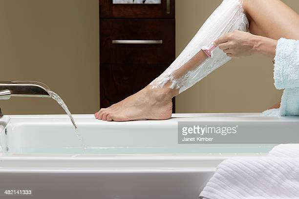 Caucasian woman shaving her legs at bathtub