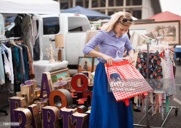 Caucasian woman shopping for apron in flea market