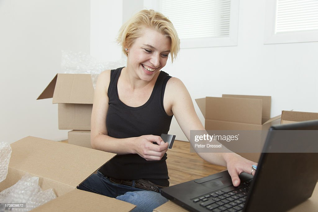 Caucasian woman shopping online in new home : Stock Photo