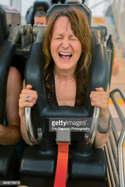 Caucasian woman shouting on roller coaster