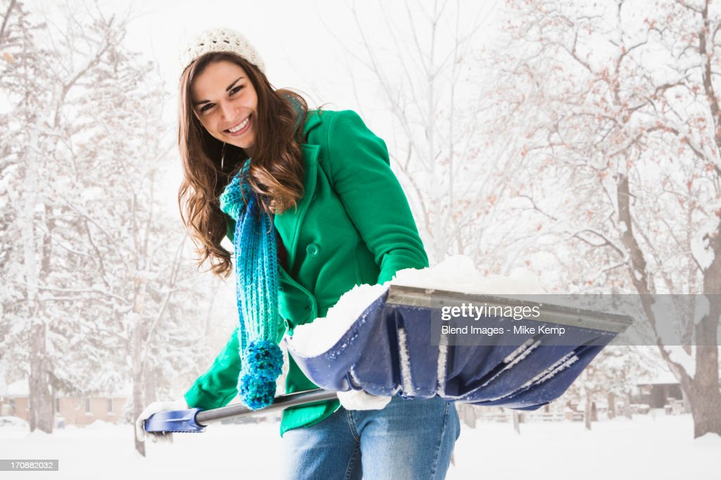 Caucasian woman shoveling snow outdoors