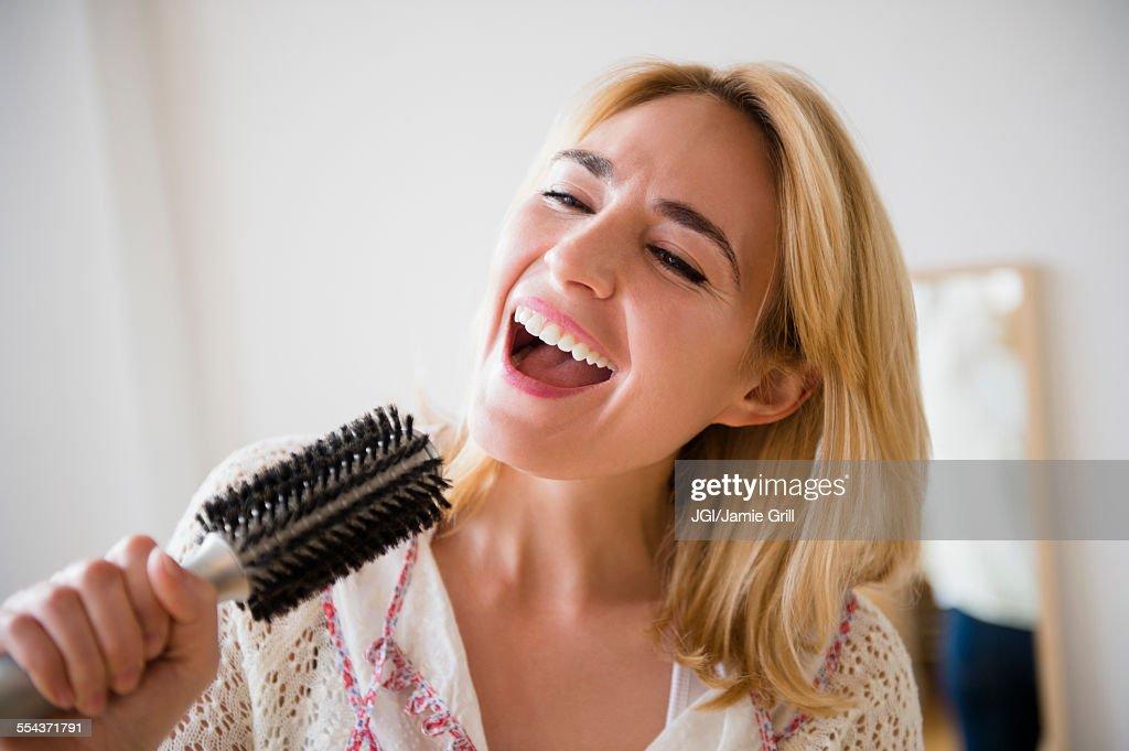 Caucasian woman singing into hairbrush