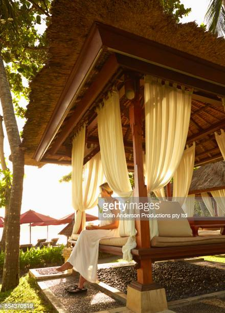 Caucasian woman sitting in cabana