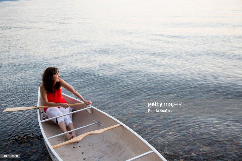 Caucasian woman sitting in canoe in lake
