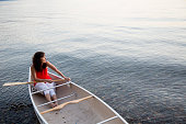 Caucasian woman sitting in canoe in lake