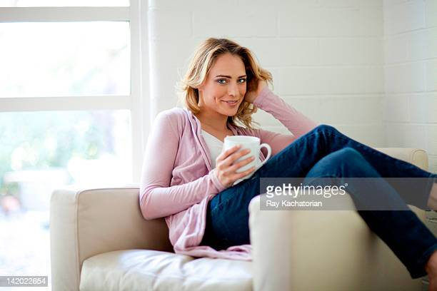 Caucasian woman sitting in chair drinking coffee