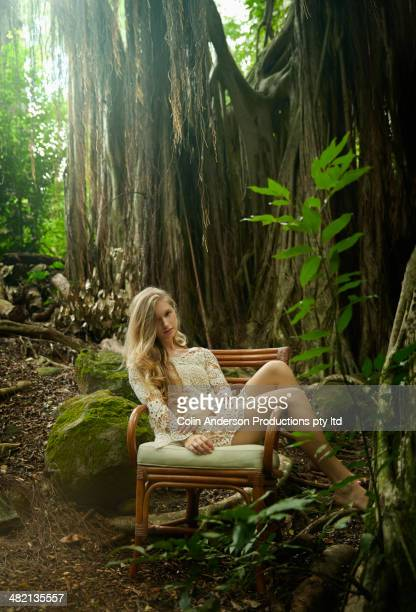 Caucasian woman sitting in chair under banyan trees