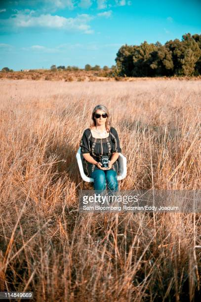 Caucasian woman sitting in field with old-fashioned camera