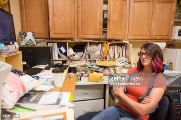 Caucasian woman sitting in messy office