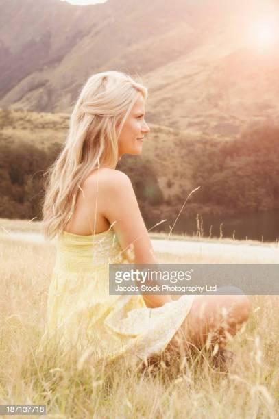Caucasian woman sitting in tall grass