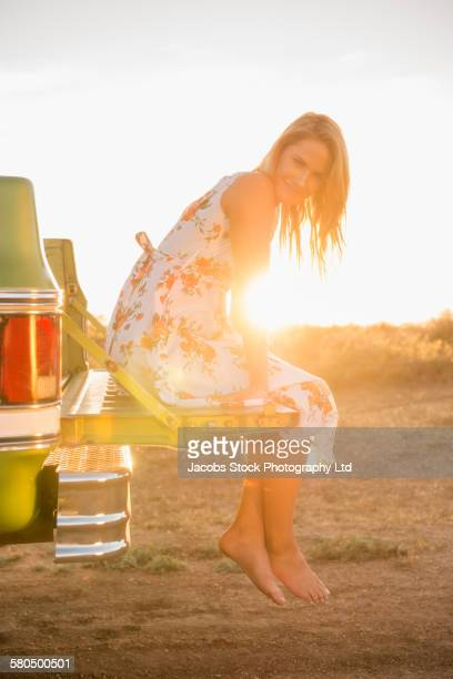 Caucasian woman sitting in truck bed on rural road
