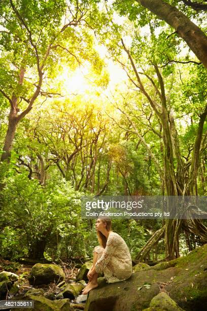 Caucasian woman sitting in woods