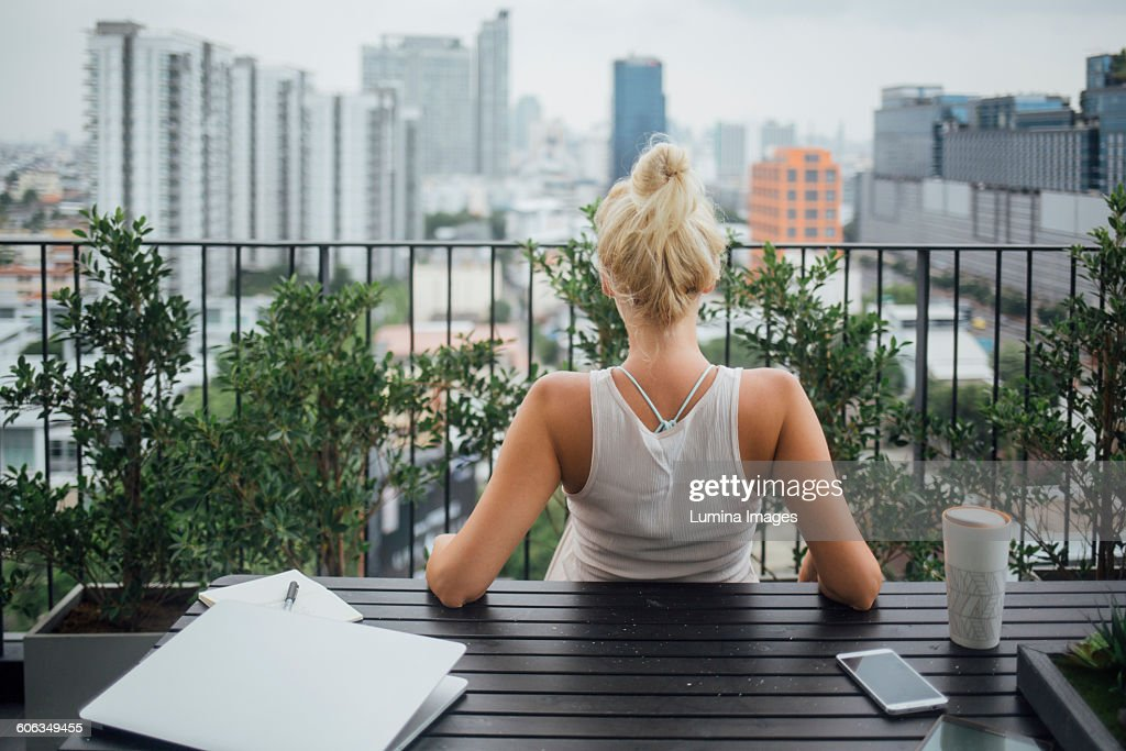 Caucasian woman sitting on balcony : Stock Photo