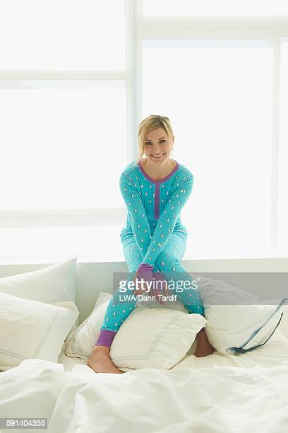 Caucasian woman sitting on bed