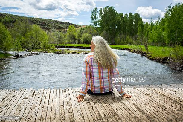 Caucasian woman sitting on dock at river