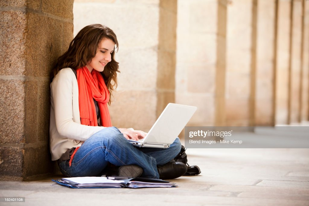 Caucasian woman sitting on ground with laptop : Stock Photo