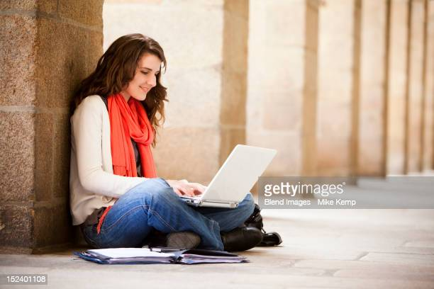 Caucasian woman sitting on ground with laptop