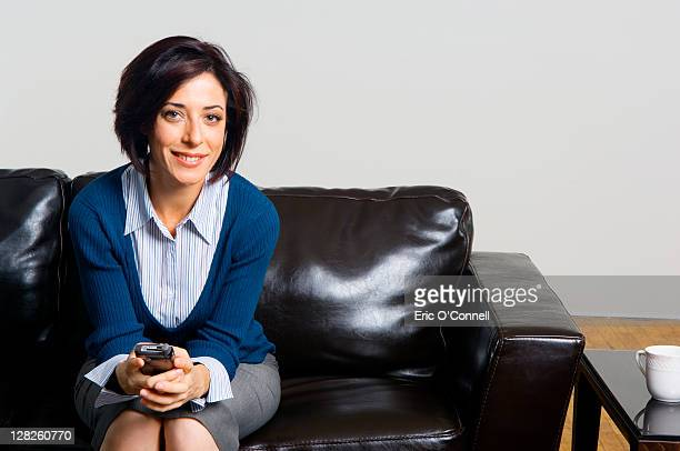 Caucasian woman sitting on leather couch with cell phone