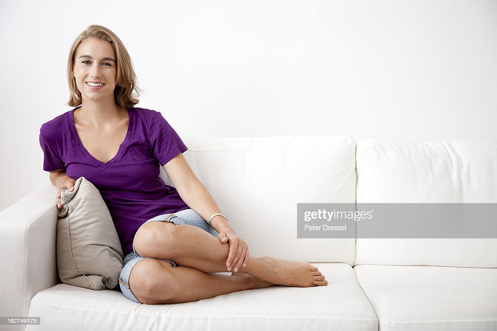 Caucasian woman sitting on sofa : Stock Photo