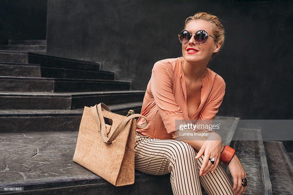Caucasian woman sitting on stairs : Stock Photo