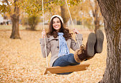 Caucasian woman sitting on swing in autumn leaves