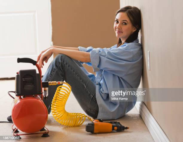Caucasian woman sitting with compressor and nail gun