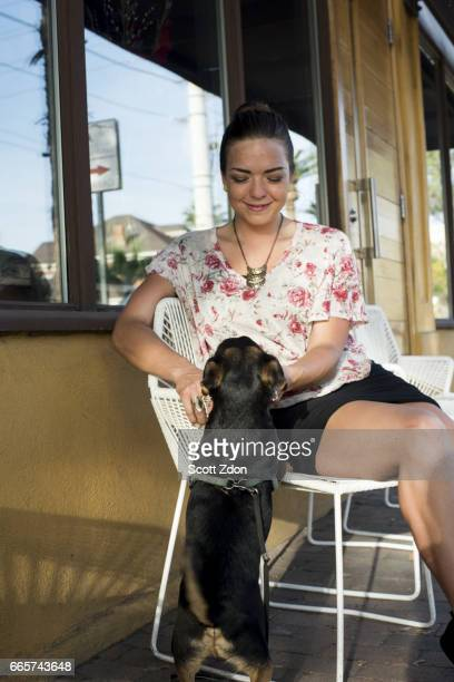Caucasian woman sitting with dog at neighborhood cafe.