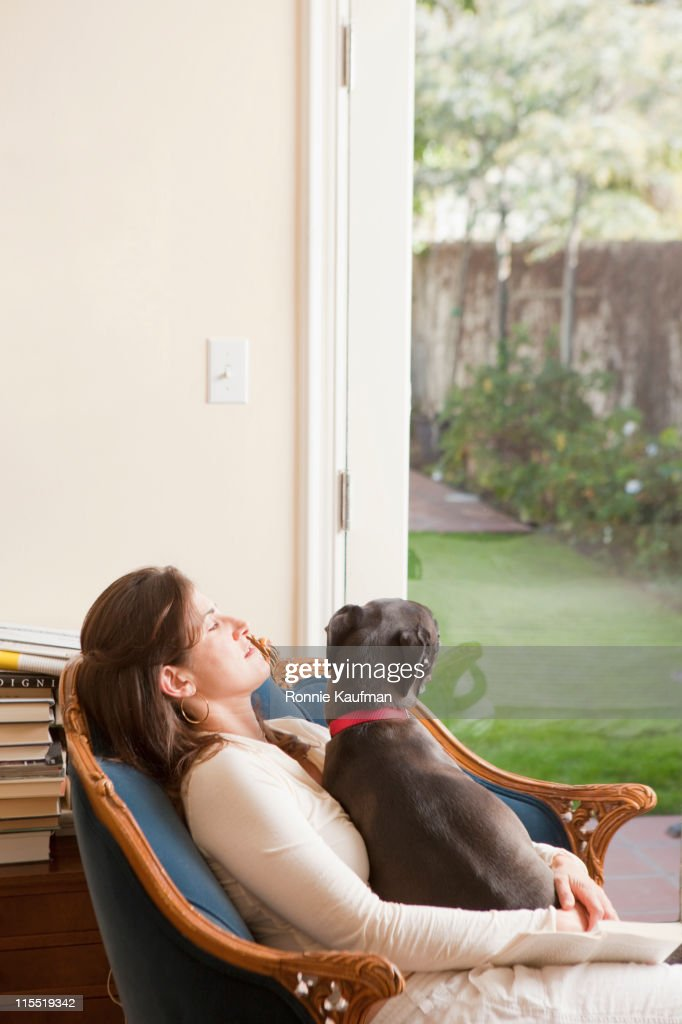 Caucasian woman sitting with dog : Stock Photo