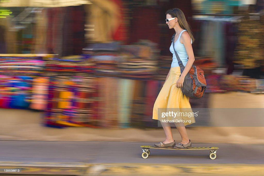 Caucasian woman skateboarding on sidewalk : Stock Photo