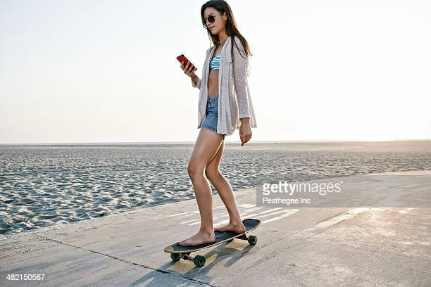 Caucasian woman skating on beach