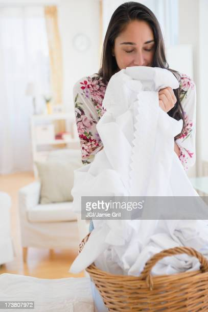 Caucasian woman smelling fresh laundry