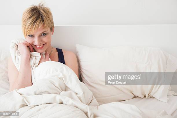 Caucasian woman smiling in bed