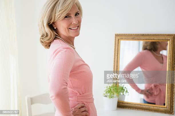 Caucasian woman smiling in mirror