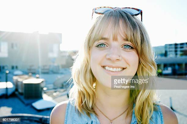 Caucasian woman smiling on urban rooftop