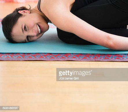 Caucasian woman smiling on yoga mat