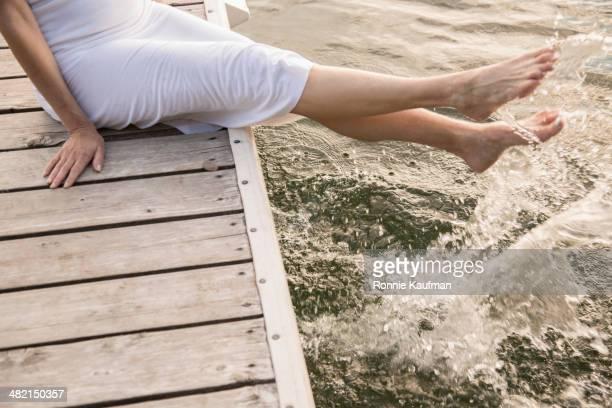 Caucasian woman splashing in water from wooden dock