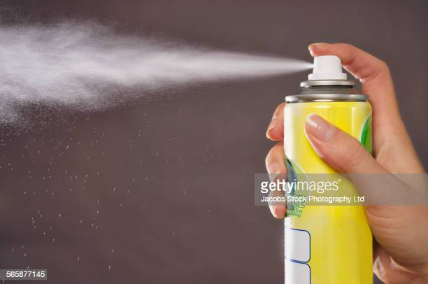 Caucasian woman spraying aerosol can
