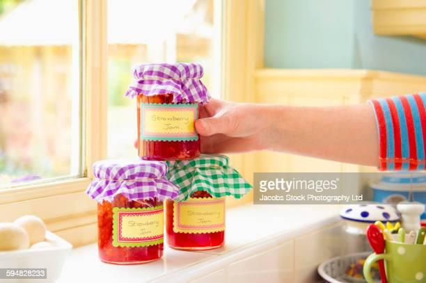 Caucasian woman stacking jam jars in kitchen