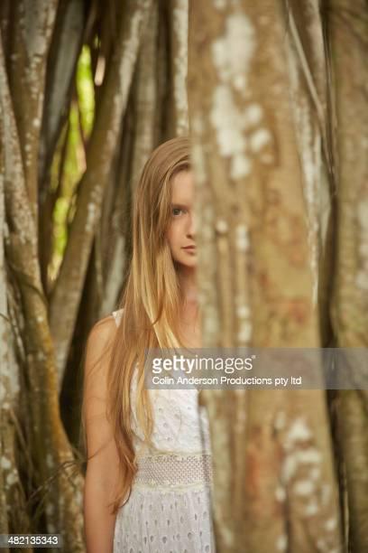 Caucasian woman standing behind banyan tree