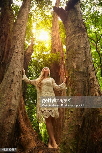 Caucasian woman standing below trees in forest