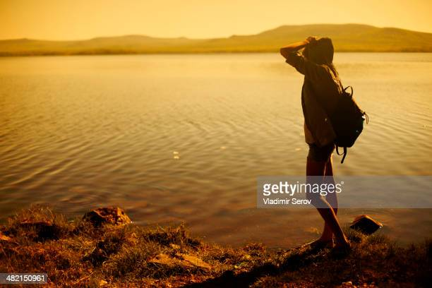 Caucasian woman standing by still rural lake