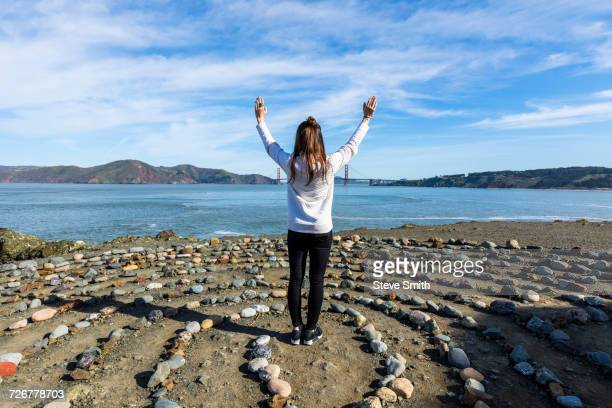 Caucasian woman standing in circle of rocks near ocean