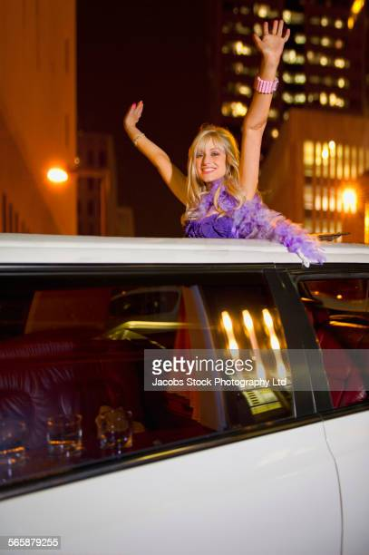 Caucasian woman standing in limousine skylight at night