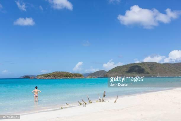 Caucasian woman standing in ocean on tropical beach