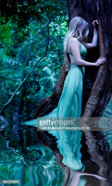 Caucasian woman standing in pool in forest