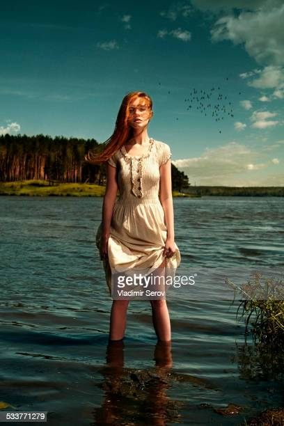 Caucasian woman standing in remote lake