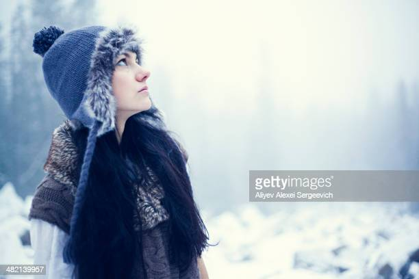 Caucasian woman standing in snowy woods
