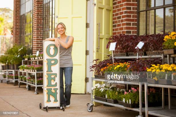 Caucasian woman standing near flower shop open sign