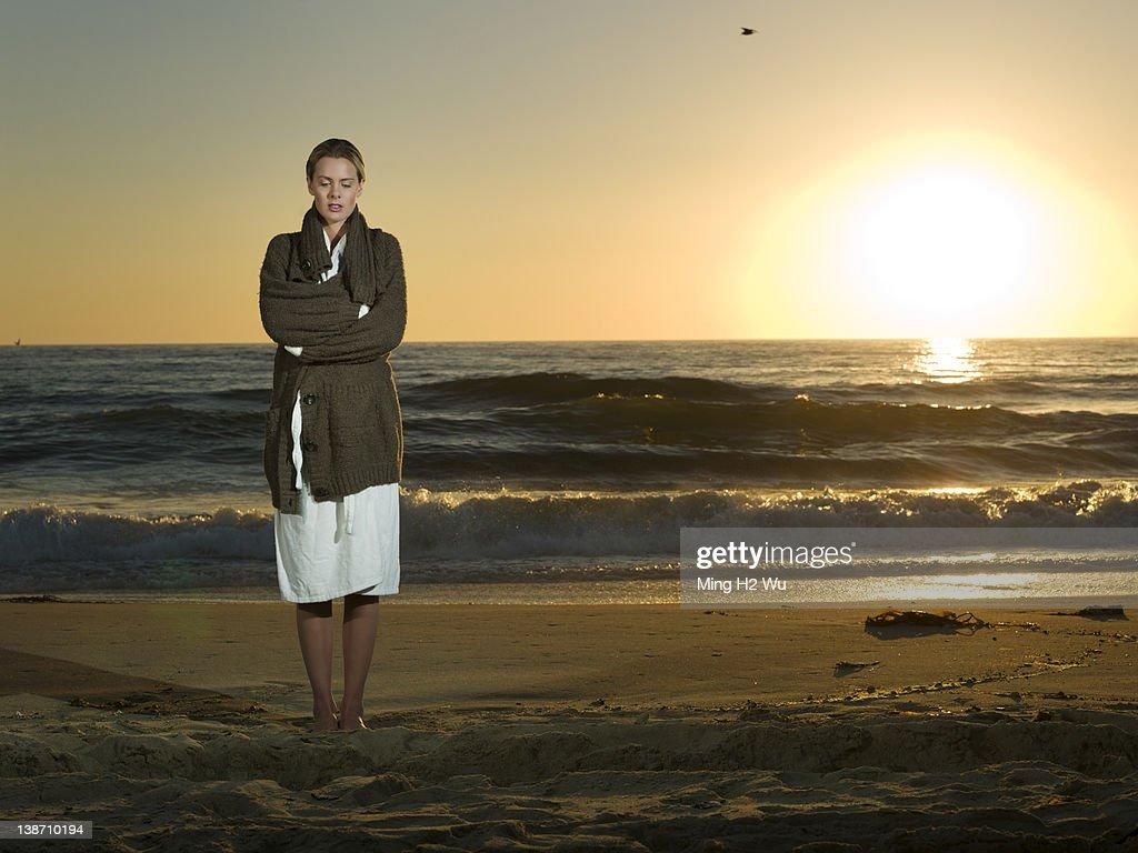 Caucasian woman standing on beach at sunset : Stock Photo
