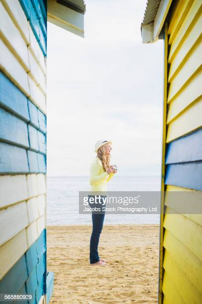 Caucasian woman standing on beach near colorful huts